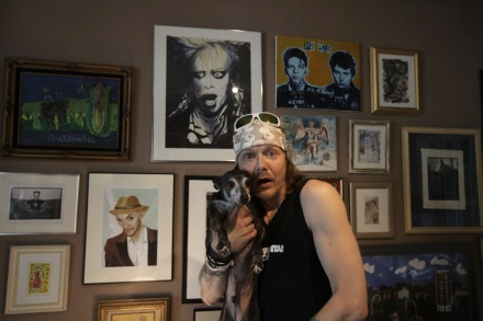 "Bjorn and Pharoh standing in front of a portrait painted by late artist and performer Holly Brown as a gift for Bjorn's 26th birthday; Frank Sinatra/Sid Vicious ""My Way"" painting on top right by Gene Evans at Lucky Star Gallery"